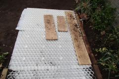 De grond wordt afgedekt met grindplaten zodat het grind niet wegzakt in het zand en makkelijk loopt