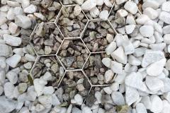 Recycling; onder oud grind van een andere tuin en nieuw, fris wit grind bovenop