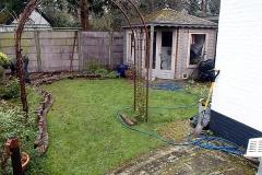 Met een tuinslang zetten we de nieuwe vorm van de border uit.