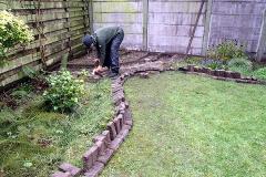 De stenen van het terras hergebruiken we; we maken er een borderrand van.